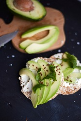 Fresh crisp bread with cream cheese and avocado on a black background. Vegetarian and diet food. Weight loss diet