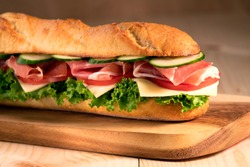 Fresh crispy baguette deli sandwich with prosciutto, cheese, tomatoes, lettuce, cucumbers on a wooden background.Close Up. Healthy concept.