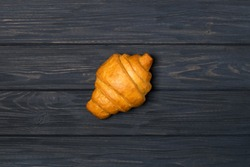 Fresh croissant on a black wooden background. Top view Copy space