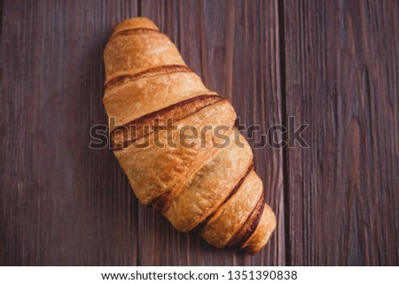 Fresh croissant on a brown wooden table. View from above. View from above. #1351390838