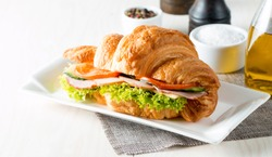 Fresh croissant or sandwich with salad, ham, jamon, prosciutto, salami, cheese, chicken, tomatoes on wooden background. Morning breakfast concept. Healthy and fast food.