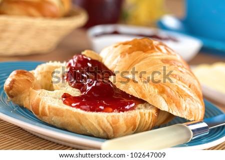 Fresh croissant with butter and strawberry jam on blue plate (Selective Focus, Focus on the front of the upper croissant half and the strawberry piece in the middle of the image)