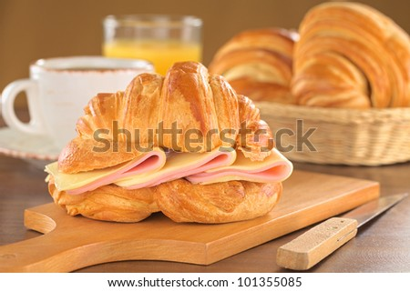 Fresh croissant with ham and cheese on wooden board with coffee, orange juice and bread basket in the back (Selective Focus, Focus on the front of the croissant and the ham and cheese slices)