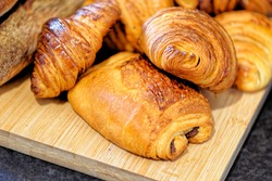 Fresh croissants and pain au chocolate, puff pastry and buttered french croissant on a plate. Food and breakfast concept. Detail of desserts and fresh pastries