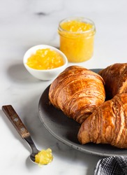 Fresh croissants. Freshly baked french croissants with jam on light grey background.