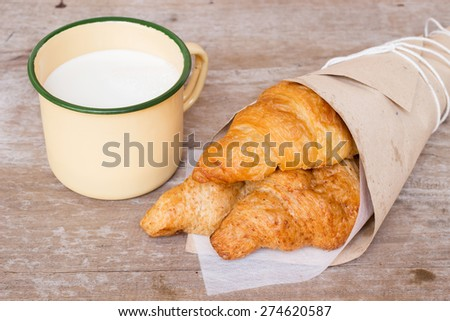 Fresh croissants in a paper wrap with milk from farm in a vintage glass