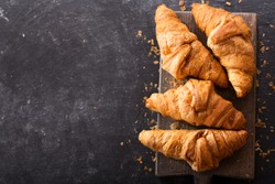 fresh croissants on a wooden board, top view