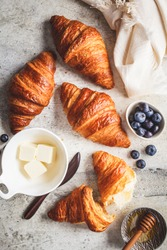 Fresh croissants with blueberries and honey, gray background.