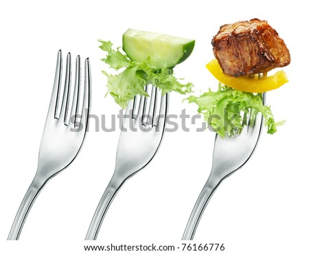 fresh cucumber, meat and salad on a fork. Isolated