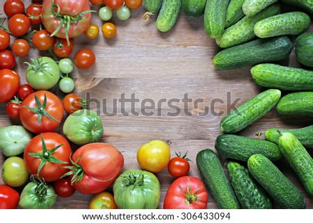 Fresh cucumbers, red and green tomatoes on a table with a blank space in the center in the center, the top view. A place for your text. Tomatoes mature and immature.