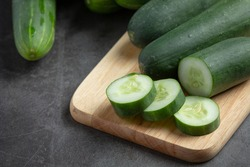 fresh cucumbers sliced on dark background