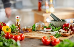 Fresh culinary herbs, spices and salad ingredients with a stone pestle and mortar on a counter in a kitchen during preparation of the dinner