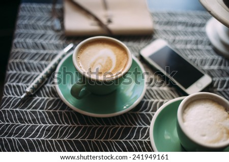 Fresh cup of cappuccino in a green cup on a coffee table with a smartphone and a notebook