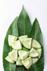 Fresh cut mango placed on  leaves isolated on white background.