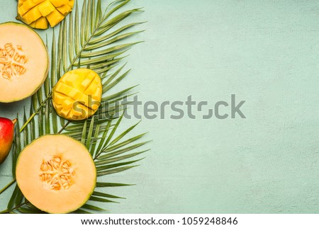 fresh cut melon and mango laid on tropical leaves on a blue rustic background, space for text, top view flat lay #1059248846