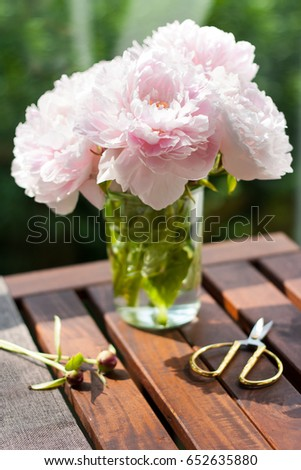 Fresh cut peonies in a glass jar on a wooden table in the garden