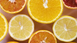 fresh cutted yellow lemons, oranges and red oranges spin on table top down view. Freshly picked sour and sweet cut citrus on turntable detailed view isolated.