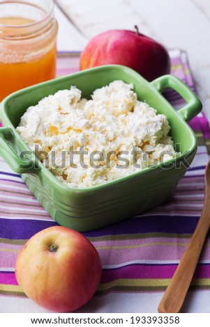 Fresh dairy products - cottage cheese, honey, apple on colorful napkin on white table. Rustic style. Bio/organic/natural ingredients. Healthy eating.
