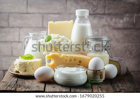 Fresh dairy products, milk, cottage cheese, eggs, yogurt, sour cream and butter on wooden table