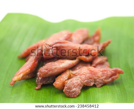 Fresh deep fried pork meat on banana leaf for food on white background