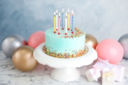 Fresh delicious birthday cake, gifts and balloons on table against color background