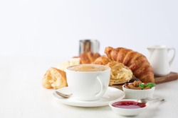 Fresh delicious breakfast with Coffee, crispy croissants, jam on white wooden background. Selective focus. Romantic french weekend concept. Copy space.