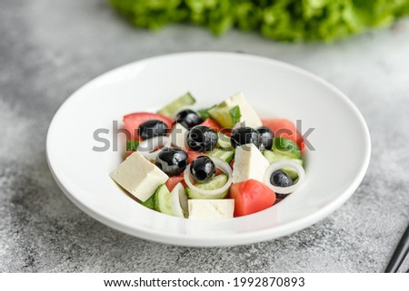 Fresh delicious Greek salad with tomato, cucumber, onions and olives with olive oil. Summer menu salads