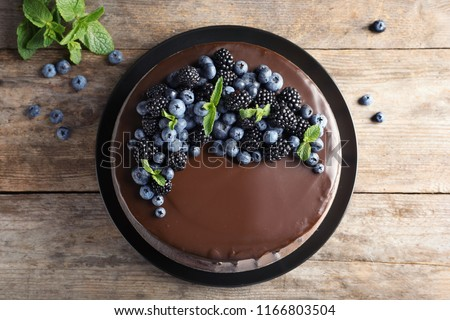 Fresh delicious homemade chocolate cake with berries on wooden table, top view