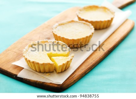 Fresh delicious lemon dessert presented nicely on baking paper and a serving platter, with a blue background