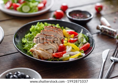Fresh delicious salad with chicken, tomato, cucumber, onions and greens with olive oil. Summer menu salads