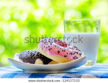 Fresh donuts and glass of milk on nature background.
