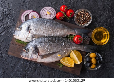Fresh Dorado fish. Raw Dorado fish and ingredient for cooking. Fresh Dorado fish, Dorado with salt, tomatoes, olives on a wooden Board. The view from the top.