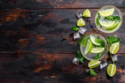 Fresh drink lemonade mojito. Mojitos with mint leaves, lime and ice. Black wooden background. Top view. Copy space