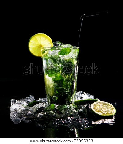 Fresh drink with ice, green mint and lime on black background