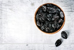 Fresh dry prunes on white rustic table. Dried plums in wooden bowl, top view on white of prune.