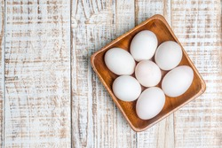 Fresh duck eggs on wooden background.