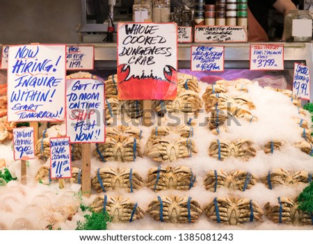 Fresh Dungeness crab and Cocktail Shrimp on ice for sale with price at Pikes Place Fish Market in Seattle, Washington, USA #1385081243