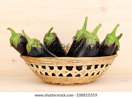 Fresh eggplants in basket on wooden background