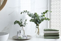 Fresh eucalyptus branches and cosmetic products on countertop in bathroom