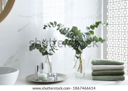 Fresh eucalyptus branches and cosmetic products on countertop in bathroom Foto stock ©