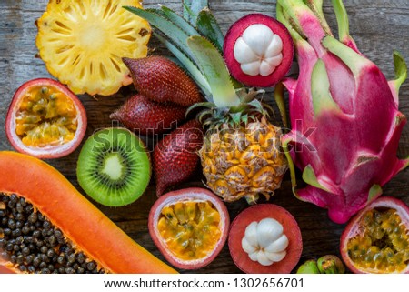 Fresh exotic tropical fruits - dragon fruit, kiwi, snake fruit (salak), pineapple, mangosteen fruit, passion fruit (maracuya) and papaya on the wooden background. Fresh fruits composition, top view