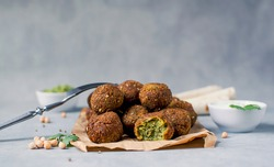 Fresh falafel balls on a black gray background with yoghurt sauce. Vegetarian food, diet, proper nutrition.