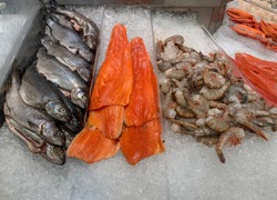 Fresh farm rainbow trout and steelhead trout fillets and wild raw U15 shrimp on top of crushed ice at a fish market.