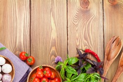 Fresh farmers tomatoes and basil on wood table. View from above with copy space
