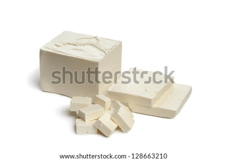 Fresh Feta cheese with slices and cubes on white background