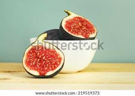 fresh figs in a bowl on wooden table, retro blue background  - stock photo