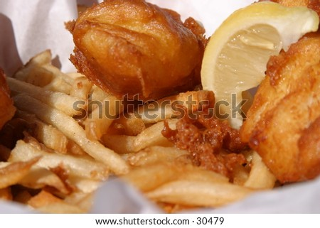 fresh fish and chips in a wicker basket with butcher paper and a lemon wedge are about to be eaten by the photographer