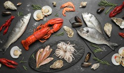 Fresh fish and different seafood on black table, flat lay
