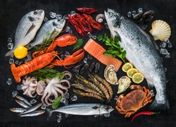 Fresh fish and seafood arrangement on black stone background