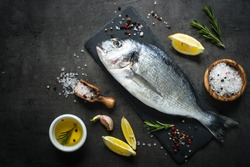 Fresh fish dorado. Dorado and ingredients for cooking at black slate table. Top view with copy space.